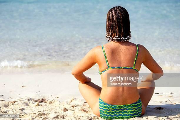 Young woman in bikini and braided hair doing Yoga