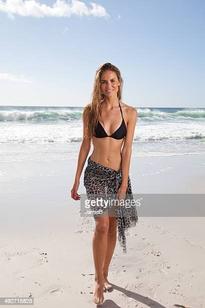 young woman in bikini and sarong walking on the beach - sarong stock photos and pictures