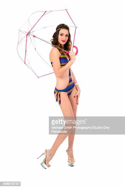 Young woman in bikini and with clear umbrella