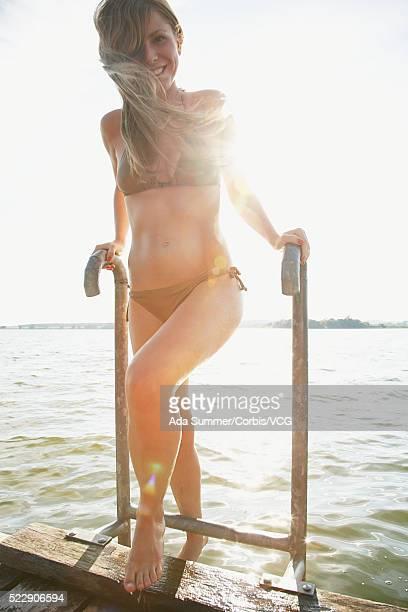 Young woman in bikini by lake