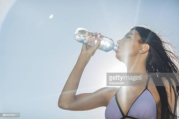 Young woman in bikini drinking water from bottle