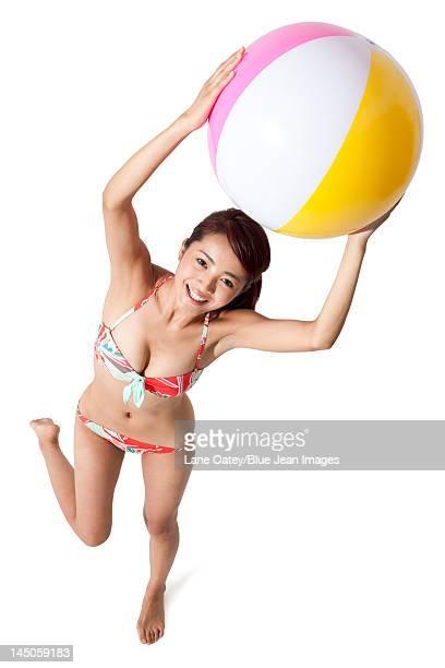 Young woman in bikini holding a ball