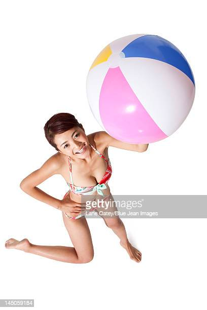 Young woman in bikini holding a ball