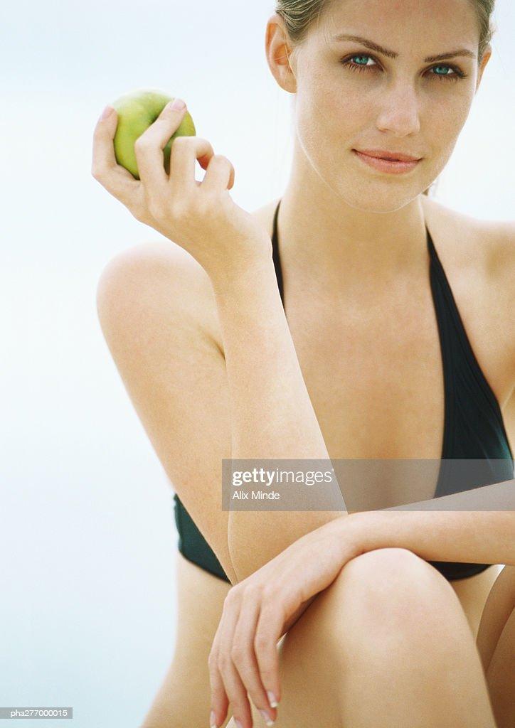 Young woman in bikini holding apple, looking at camera : Stockfoto
