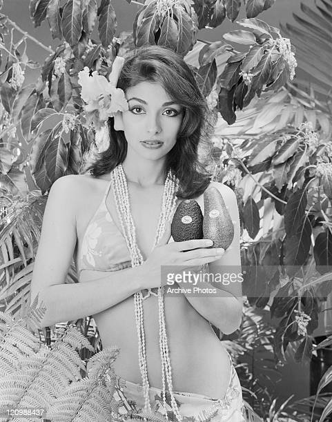 Young woman in bikini holding avocados portrait