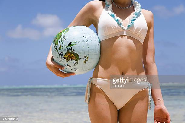 Young woman in bikini holding balloon in form of Earth, mid section