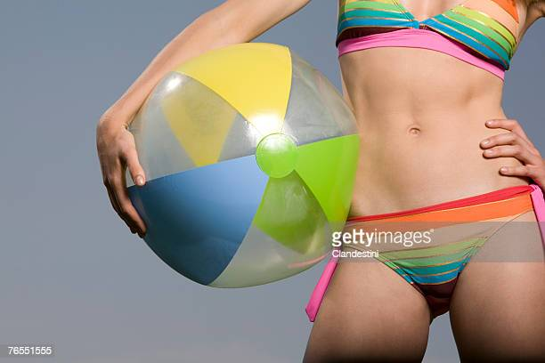 Young woman in bikini holding beach ball, mid section, close-up
