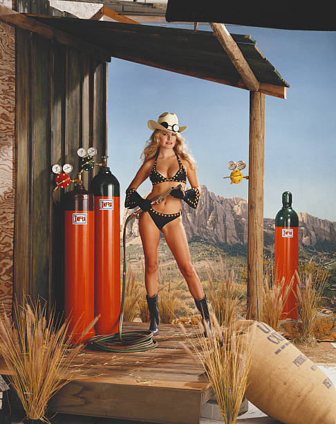 Young woman in bikini holding pipe of oxygen cylinders