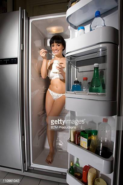Young woman in bikini inside the refrigerator
