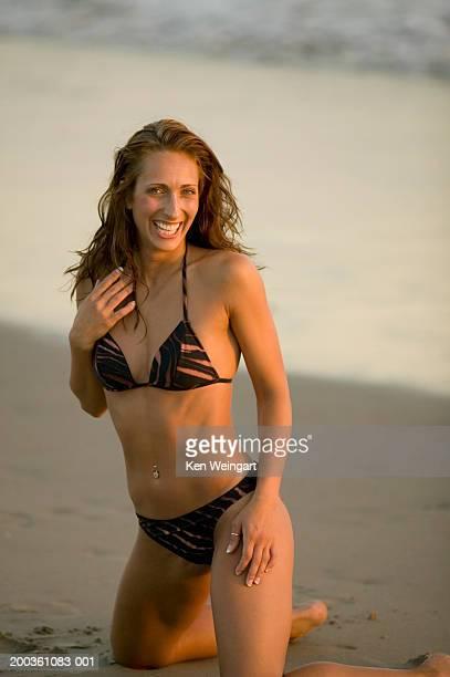 Young woman in bikini, kneeling on beach, smiling, portrait
