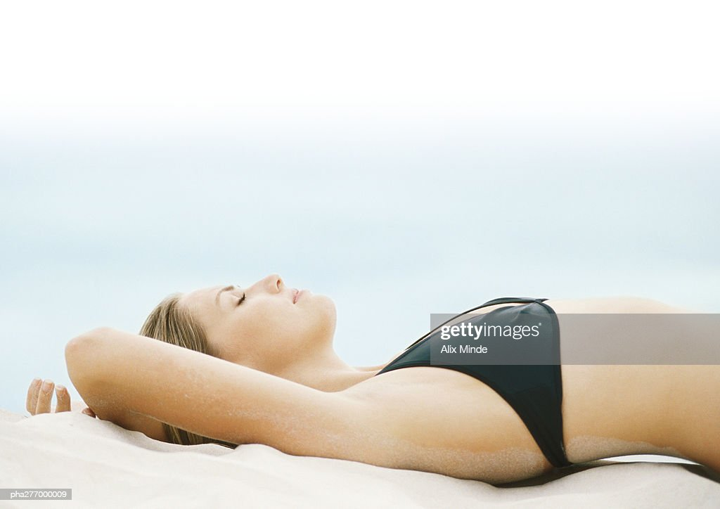 Young woman in bikini lying on sand with eyes closed, side view : Stockfoto