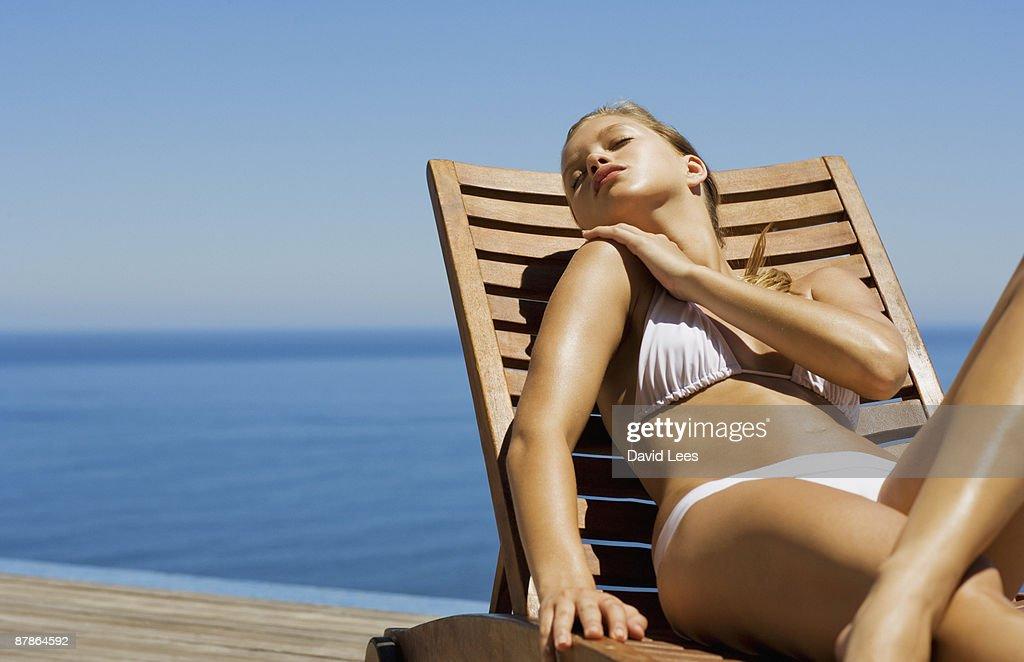 Young woman in bikini lying on sun lounger by sea : Stock Photo