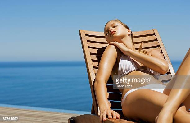 young woman in bikini lying on sun lounger by sea - sunbathing stock pictures, royalty-free photos & images