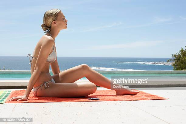 young woman in bikini relaxing near swimming pool at ocean - hair back stock pictures, royalty-free photos & images