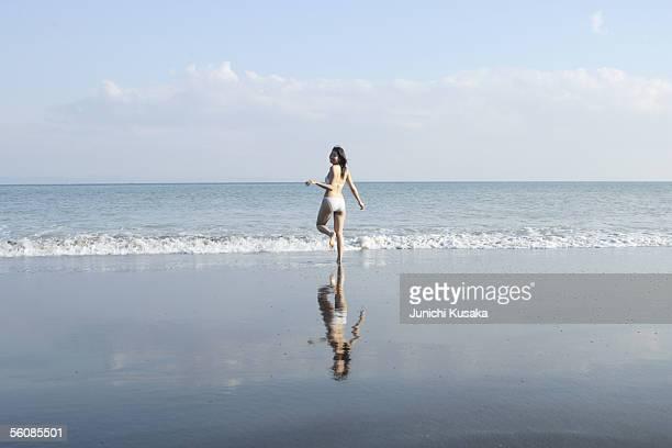A young woman in bikini running at beach, rear view
