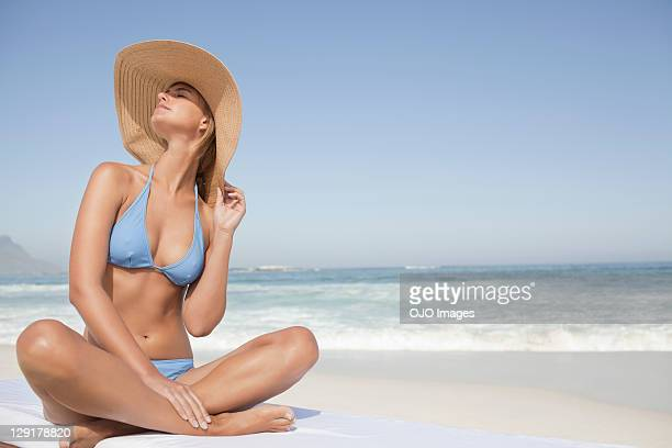 young woman in bikini sitting at beach - badkleding stockfoto's en -beelden