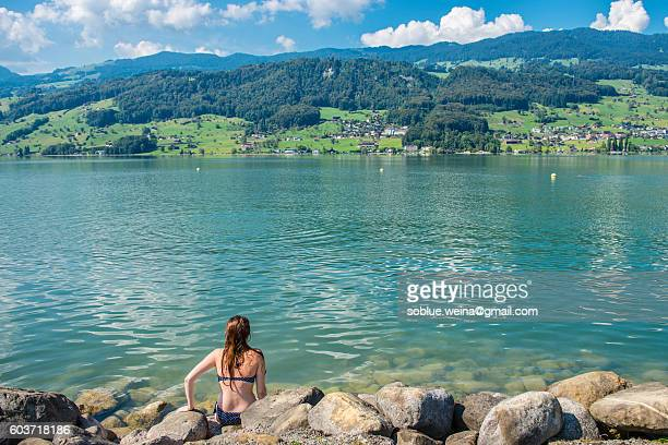 A young woman in Bikini sitting at the lakeside, enjoying the view of Sarnersee lake Sarnen and the alps mountains in Switzerland