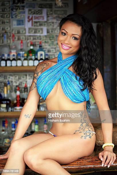 Young woman in bikini sitting on bar counter