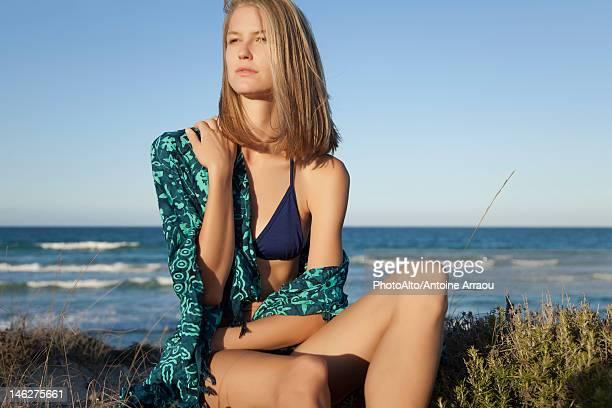 Young woman in bikini sitting on beach, portrait