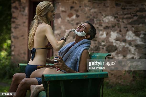 Young woman in bikini sitting on boyfriends lap applying shaving cream at holiday cottage