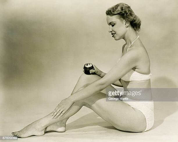 jovem mulher de biquíni sentado, colocando creme na perna, & (b w - silhueta de corpo feminino preto e branco - fotografias e filmes do acervo