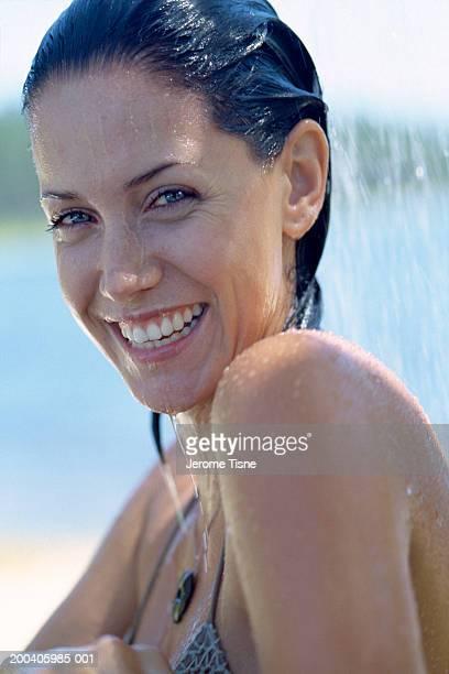 young woman in bikini smiling under outdoor shower, portrait, close-up - jeune femme sous la douche photos et images de collection
