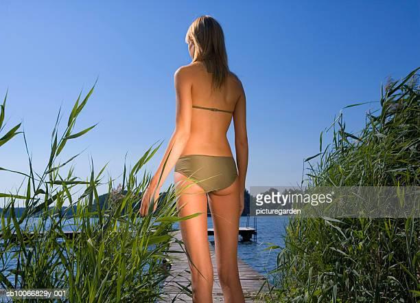 Young woman in bikini standing on jetty, rear view