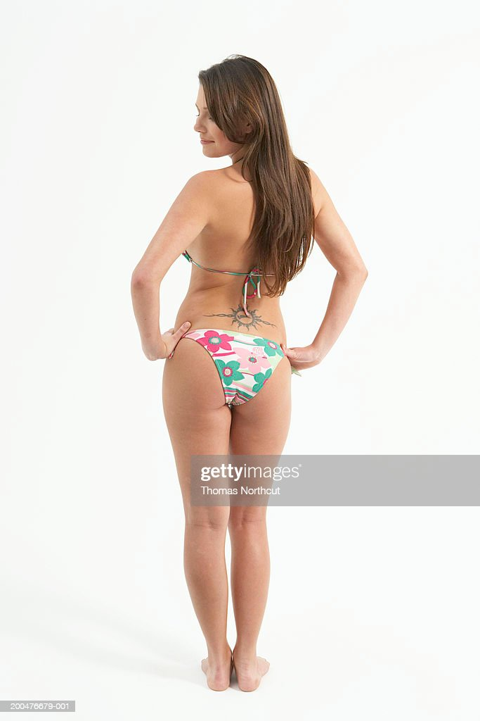 Young woman in bikini standing with hands on hips, rear view : Stock Photo