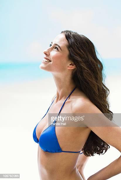 Young woman in bikini top smiling, side view