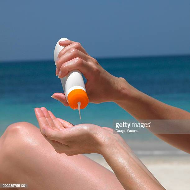 Young woman in bikini using sunscreen, close up