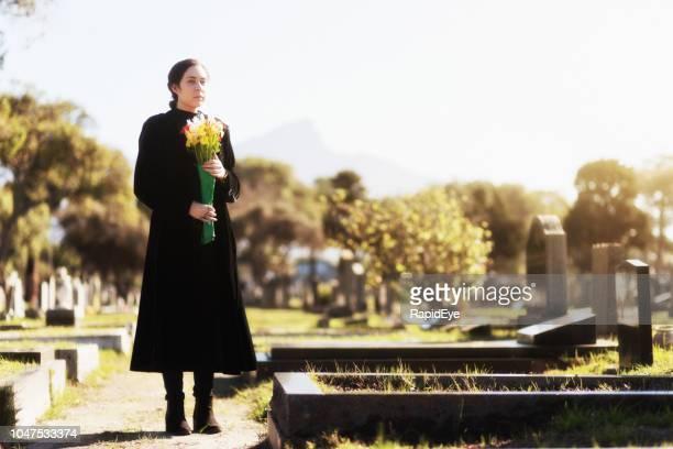 joven mujer de negro llevando flores a la tumba - mausoleo fotografías e imágenes de stock