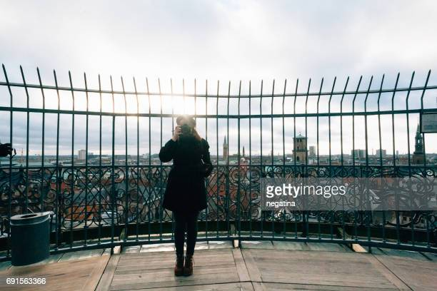 young woman in black coat takes photograph on the observation deck in Copenhagen, Denmark