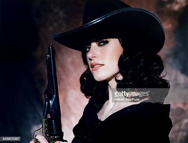 young woman in black cowboy hat with pistol - cowgirl hairstyles stock photos and pictures