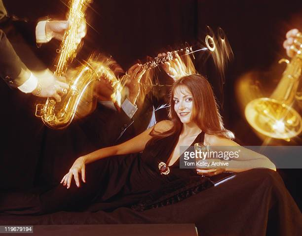young woman in black dress holding drink and surrounded by musician - 1973 stock pictures, royalty-free photos & images