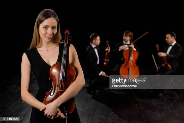 young woman in black dress holding violin. - soloist stock photos and pictures