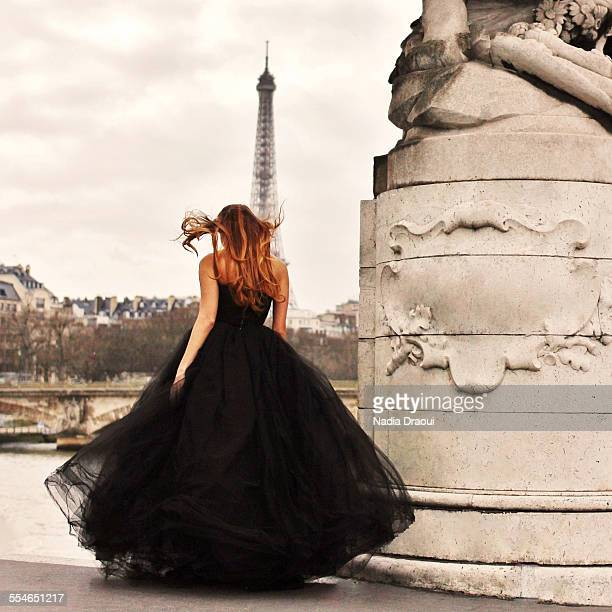 young woman in black dress looking at eiffel tower - french women stock photos and pictures