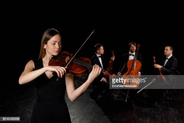 young woman in black dress playing violin - string instrument stock photos and pictures