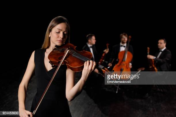 Young woman in black dress playing violin