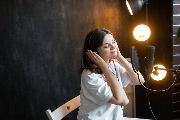 Young woman in black headphones drinking coffee and making recordings podcast while sitting at table at home. Blogger concept.