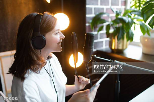 young woman in black headphones making recordings podcast at home. - radio stock pictures, royalty-free photos & images