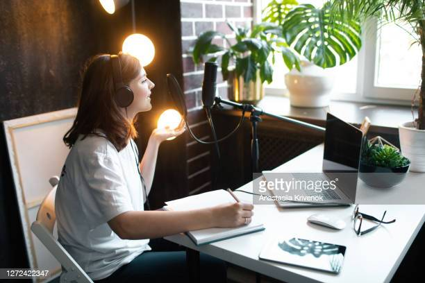 young woman in black headphones making recordings podcast at home. - recording studio stock pictures, royalty-free photos & images
