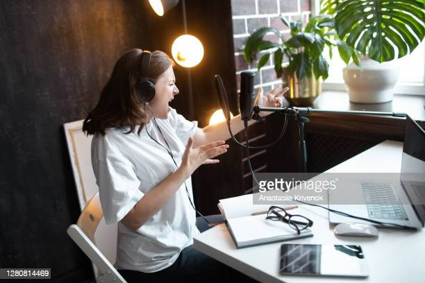 young woman in black headphones making recordings podcast at home. - live broadcast stock pictures, royalty-free photos & images