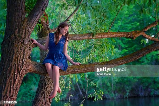 Young woman in blue dress sits on tree branch