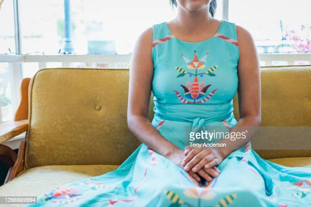 young woman in blue dress sitting on gold sofa - sleeveless dress stock pictures, royalty-free photos & images