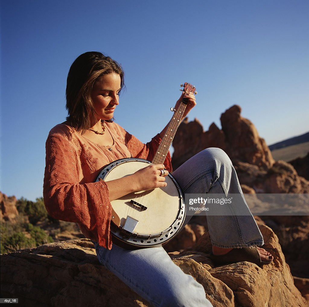 young woman in blue jeans red shirt sits on boulder playing a banjo blue sky rock croppings behind : Foto de stock