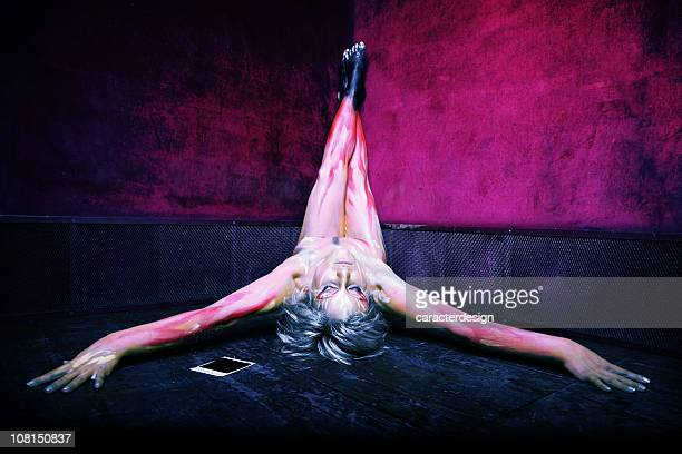 Young Woman in Body Painted Flames Laying on Ground