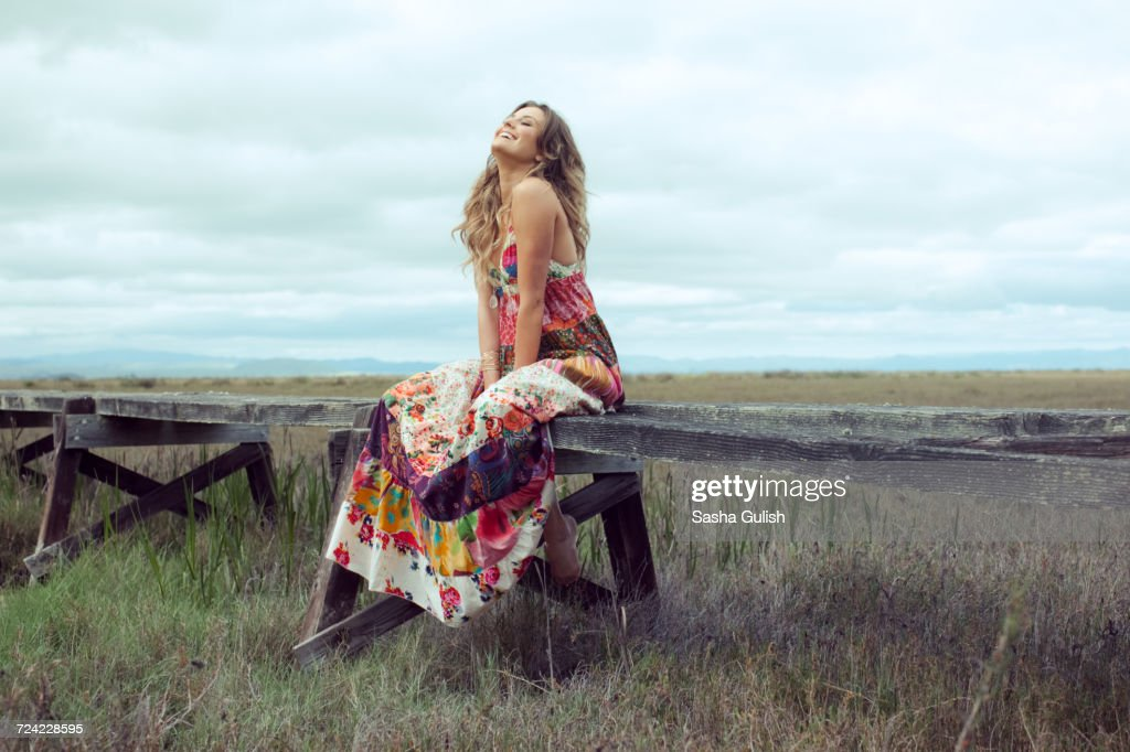 Young woman in boho maxi dress sitting on elevated wooden walkway in landscape : Stock Photo