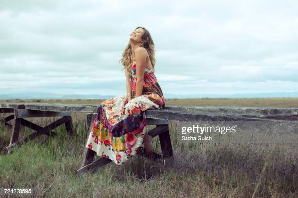 young woman in boho maxi dress sitting on elevated wooden walkway in landscape - long dress stock pictures, royalty-free photos & images