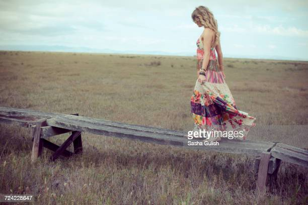 young woman in boho maxi dress walking on elevated wooden walkway in landscape - robe longue photos et images de collection