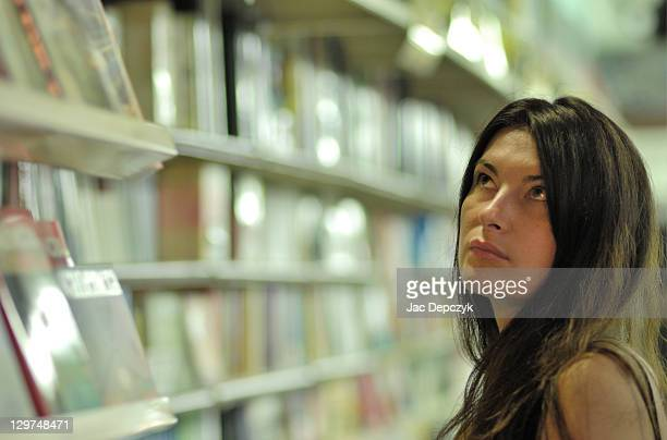 young woman in bookshop - depczyk stock pictures, royalty-free photos & images